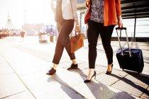 Businesswomen with luggage walking outside railroad station — Stock Photo