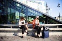 Femmes d'affaires assises sur le mur de soutènement — Photo de stock