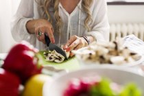 Жінка різання гриби кухні — стокове фото