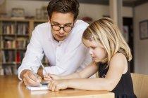 Male teacher assisting girl — Stock Photo