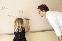 Insegnante guardando ragazza praticare la scrittura — Foto stock