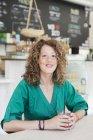 Жінка сидить за столом кафе — стокове фото