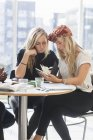 Female friends reading notes — Stock Photo