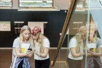 Étudiants utilisant un téléphone mobile sur les marches — Photo de stock