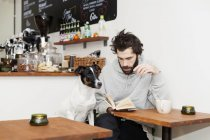 Dog with man reading book — Stock Photo