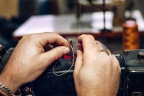 Hands inserting thread — Stock Photo