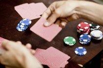 Equipaggia le mani giocando a carte a casa — Foto stock