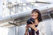 Женщина держит цифровую камеру — стоковое фото