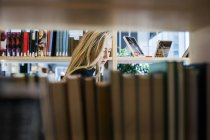 Woman seen through bookshelf — Stock Photo