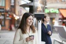 Femme avec tasse de café et téléphone portable — Photo de stock