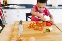 Boy chopping red bell pepper — Stock Photo