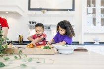 Мать с детьми готовит вместе — стоковое фото