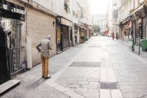 Senior man standing on sidewalk — Stock Photo