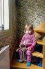 Fille tenant des jouets tout en étant assis sur les marches — Photo de stock