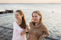 Women leaning on railing by sea — Stock Photo