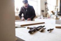 Strumenti sul tavolo con carpentiere che lavora — Foto stock