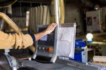 Carpenters hand using monitor — Stock Photo