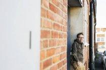 Плотник опирается на кирпичную стену — стоковое фото