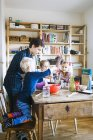 Happy father with children mixing ingredients — Stock Photo