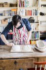 Baker making bread loaf at table — Stock Photo