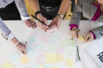 Businesswomen writing reminders at desk — Stock Photo