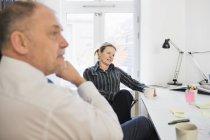 Деловые люди, сидя на столе в офисе — стоковое фото