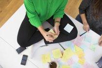 Imprenditrici che scrivono promemoria su note adesive — Foto stock