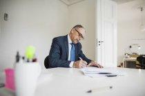 Businessman writing on documents — Stock Photo