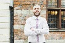 Imprenditore in piedi braccia incrociate fiducioso — Foto stock