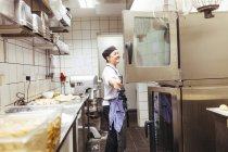 Chef looking in oven at commercial kitchen — Stock Photo