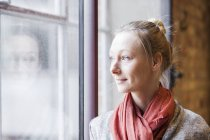 Woman looking through window in cafe — Stock Photo