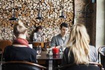 Hommes et femmes assis au restaurant — Photo de stock