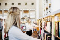 Выбор книги счастливый студентка — стоковое фото