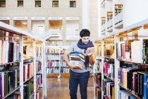 Junger Mann Auswahl Bücher in der Bibliothek — Stockfoto
