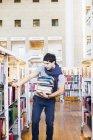 Junger Mann, die Auswahl der Bücher — Stockfoto