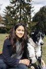 Женщина сидит с собакой смешанной породы — стоковое фото