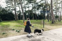 Woman walking with mixed-breed dog — Stock Photo