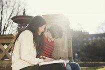 Lächelnde College-Studenten lesen Buch — Stockfoto