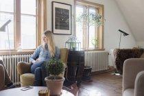 Young woman sitting on sofa — Stockfoto
