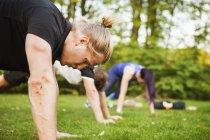 Friends doing push-ups on field — Stock Photo