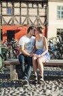 Casal beijando enquanto sentado no banco — Fotografia de Stock