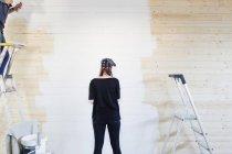 Mujer pintura pared de madera - foto de stock
