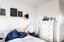 Jovem mulher fazendo cama em casa — Fotografia de Stock