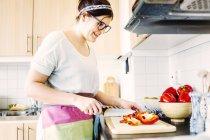 Frau schneidet rote Paprika — Stockfoto
