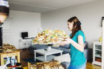 Woman carrying tray full of sandwiches — Stock Photo