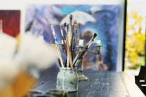 Paintbrushes in container on table — Stock Photo