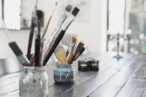 Paint brushes in containers — Stock Photo
