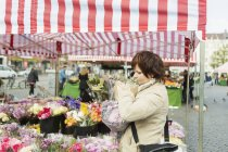 Mature woman buying bouquet — Stock Photo