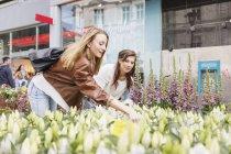 Female friends shopping flowers — Stock Photo