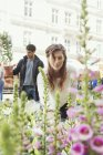 Woman touching flower at market — Stock Photo